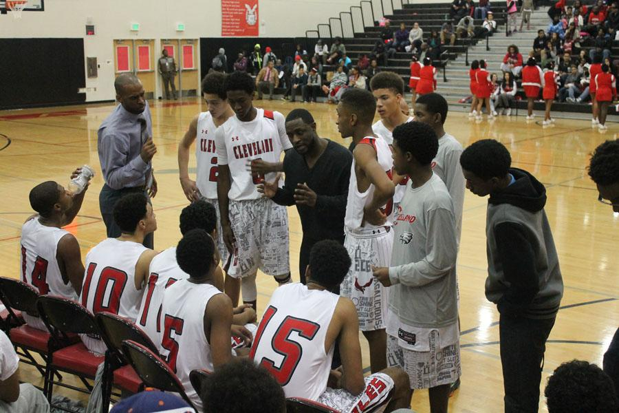 Boys' Varsity coach Jerry Petty, center, gives his players instructions during a timeout against Renton on Dec. 3. The Eagles went on to win, 65-41.