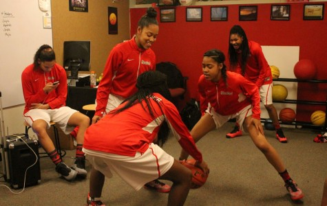 Senior Jayde Christopher, with her back facing the camera, plays a game of monkey with her cousins, sophomore twins Zareya, center, and Zakeya Flowers before the start of their game against Seattle Prep while senior Aqeelah Williams looks on in the background. Senior Joyce Harrell is seated far left.
