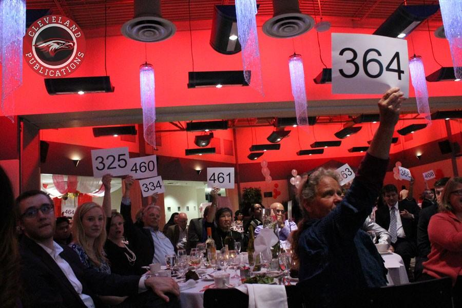 """Patrons hold their bid cards high during the """"Raise the Paddle"""" portion of Cleveland's live auction on Saturday, April 25. The event raised over $50,000 to fund various CHS activities."""