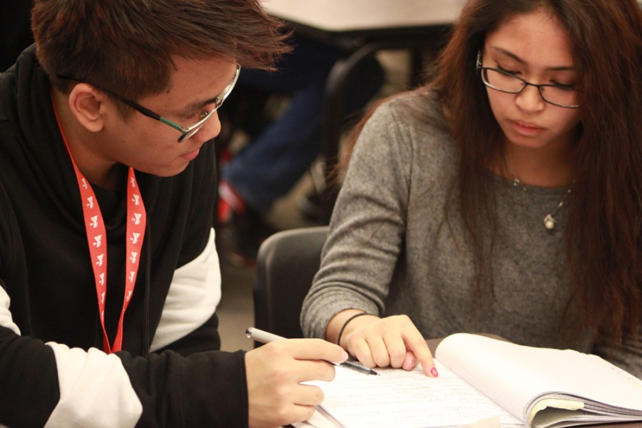 Senior Hilton Vo, left, helps junior Elyzha Abella with her math homework at CASH on Dec. 3, 2015. Vo volunteers as a tutor.