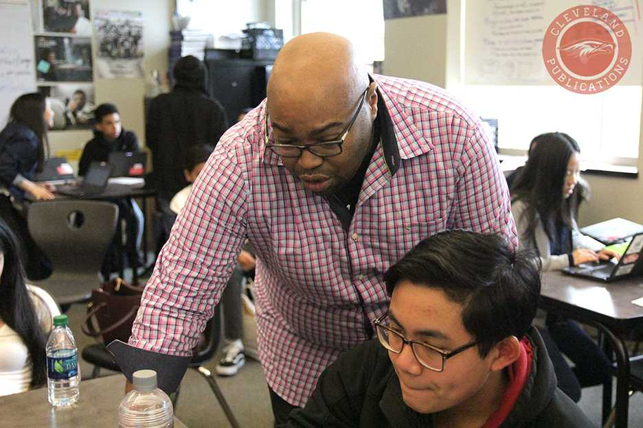 Humanities teacher Evin Shinn, one of the few teachers of color at Cleveland, looks over John Alfred Duenas' work during 5th period on Jan. 30. Shinn believes his race is why he has often been associated with his ability to maintain order in his classroom, not by his ability to teach.