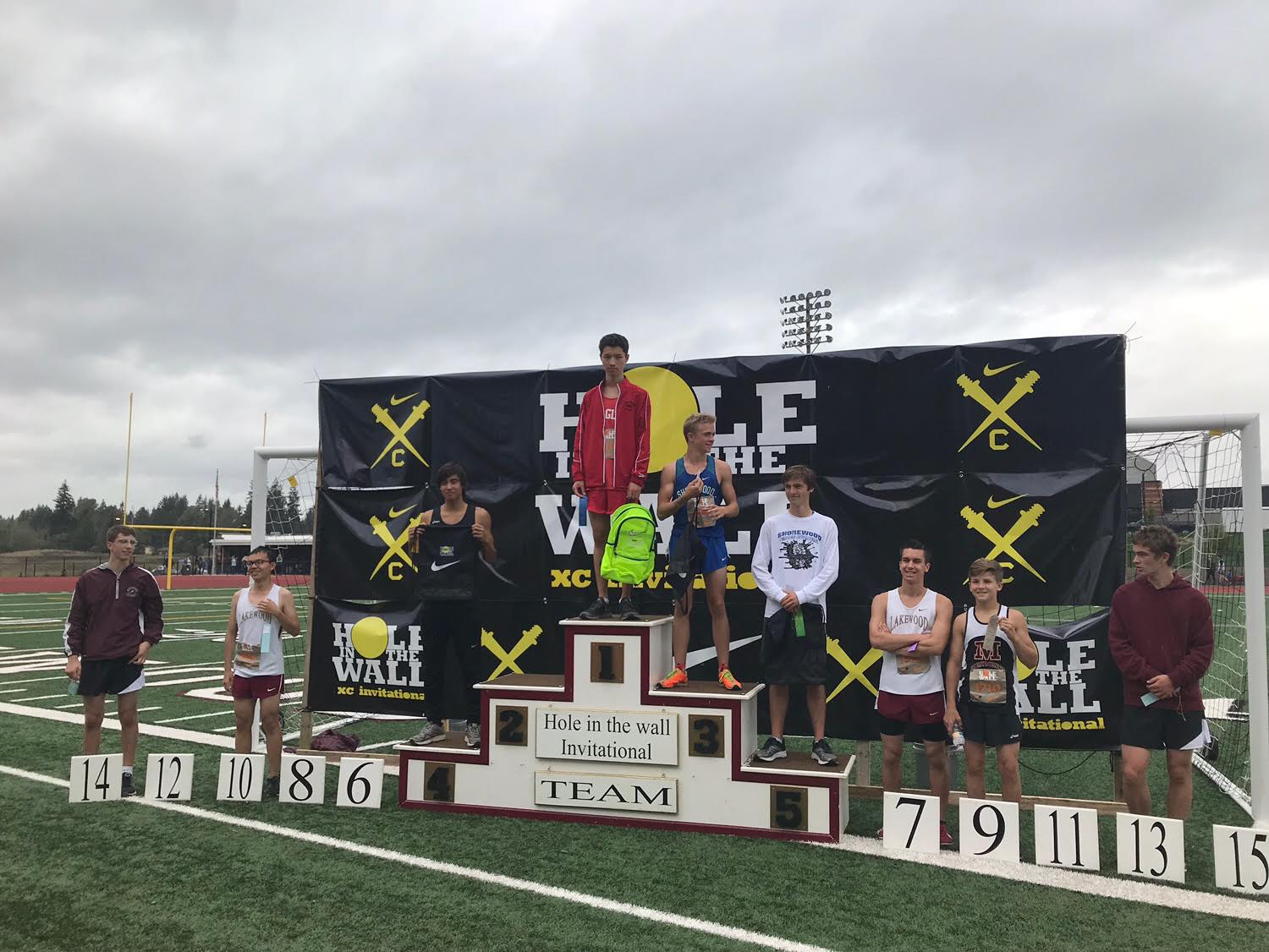 Junior Quentin Lowe, center, stands on top of the Hole in the Wall Invitational podium holding his prizes, a Nike backpack and a 1st place medal on Oct. 7.