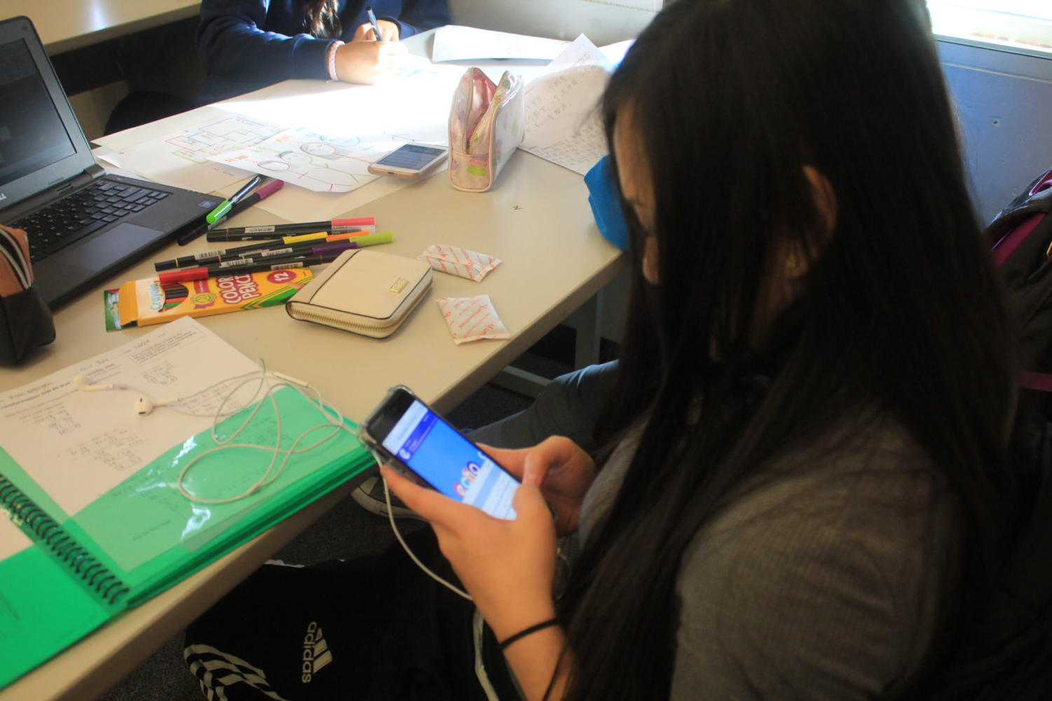 Sophomore Kim Nguyen uses her phone to check Echo during her Mandarin class on Oct. 27. Students have taken to using social media and group chats to help them prepare for class or get help with their homework.