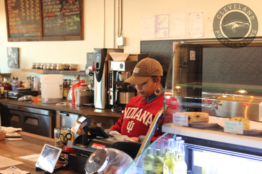 A barista tends to the register at The Station coffee shop in Beacon Hill on Dec. 5. The shop is a popular hangout for neighborhood dwellers and commuters who use the light rail.