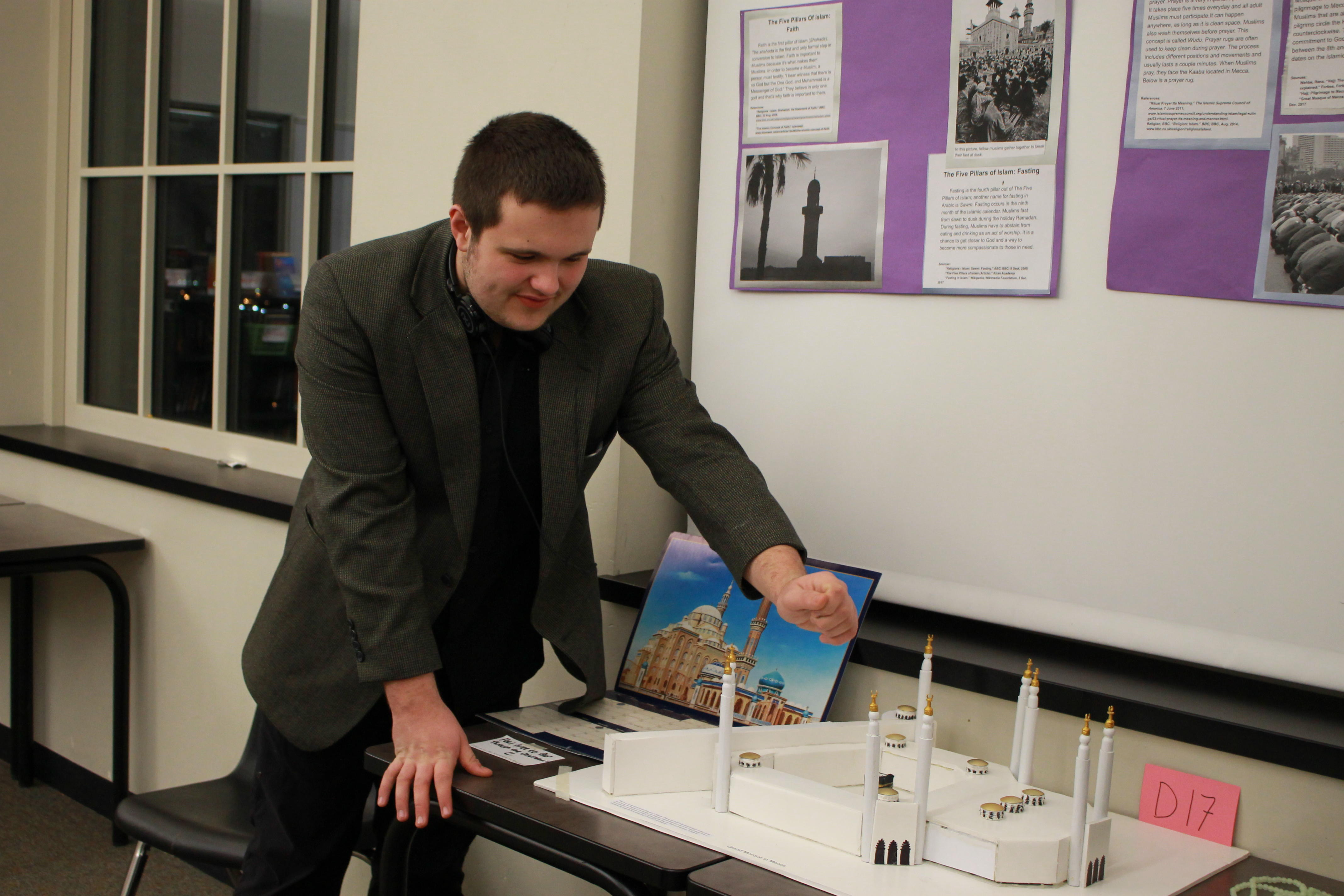 "Maxwell Brooke explains his display about Islam and the Grand Mosque in Mecca during the ""Museum of Religious Tolerance and Understanding"" on Dec. 14, 2017. In its second year, the freshman Humanities project expanded in size and added new requirements for students."