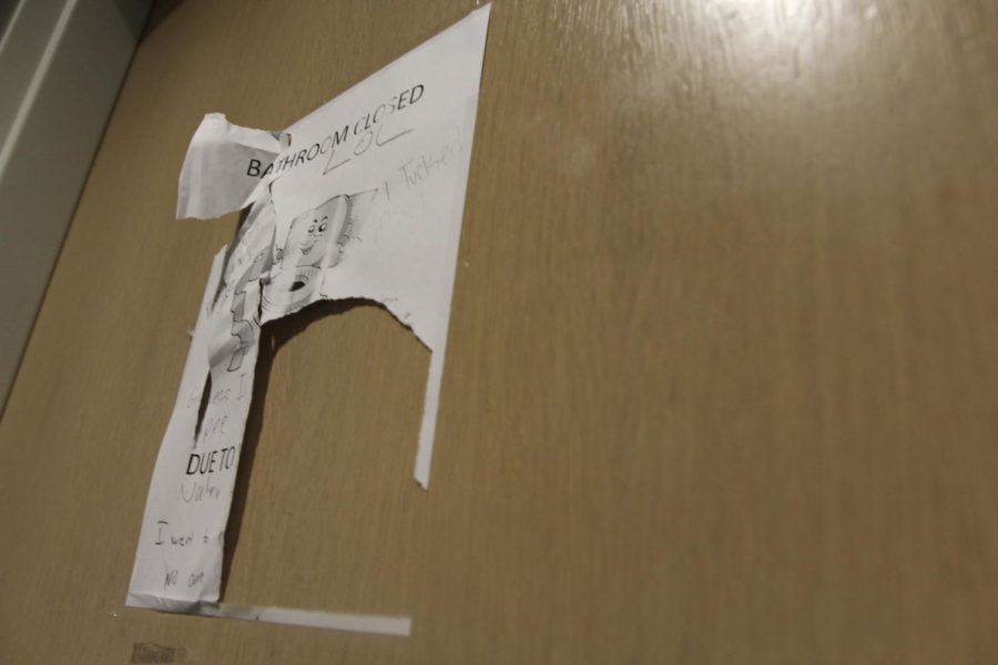 A+destroyed+closure+sign+hangs+on+one+of+the+boys+bathroom+doors+on+March+28.+The+restrooms+were+closed+after+students+kicked+holes+in+the+walls+and+ripped+out+paper+towel+dispensers.