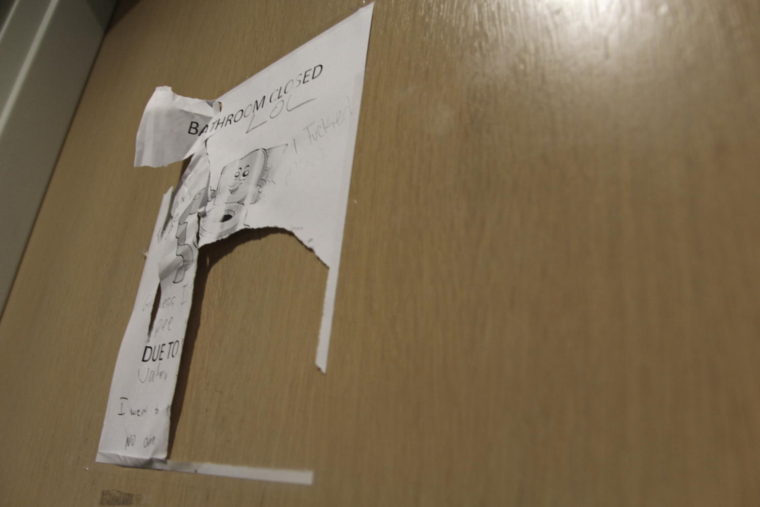A destroyed closure sign hangs on one of the boys bathroom doors on March 28. The restrooms were closed after students kicked holes in the walls and ripped out paper towel dispensers.