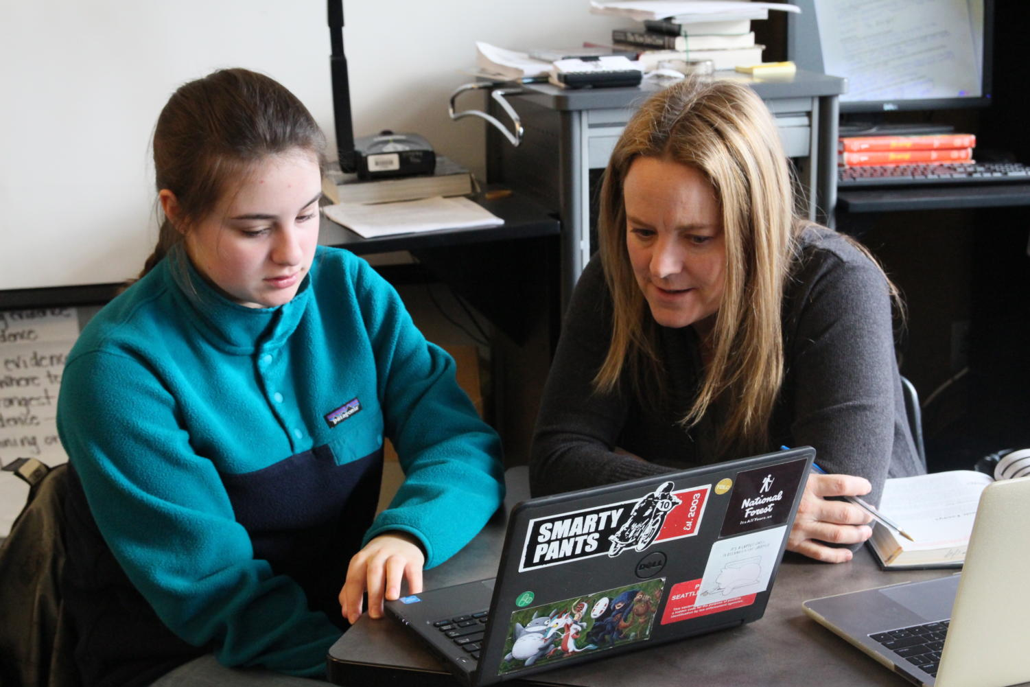Humanities teacher Rachel Evans works with sophomore Kiley Amundson on her essay during a one-on-one conference on March 13. Evans uses the feedback she receives from students to help her grow as a teacher.