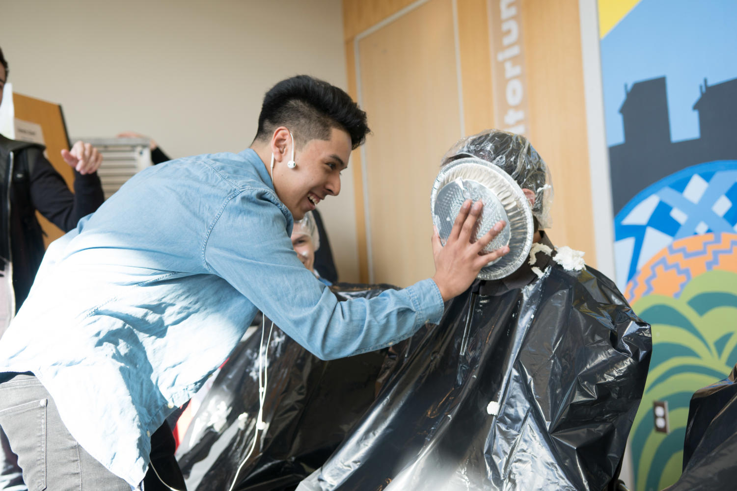 Junior Israel Ortiz Jr. lets science teacher Greg Kowalke have it during Pie A Teacher Day on March 14. This was the third year for the event where students got a chance to get revenge on teachers. This year, students were added to the panel to get pied.