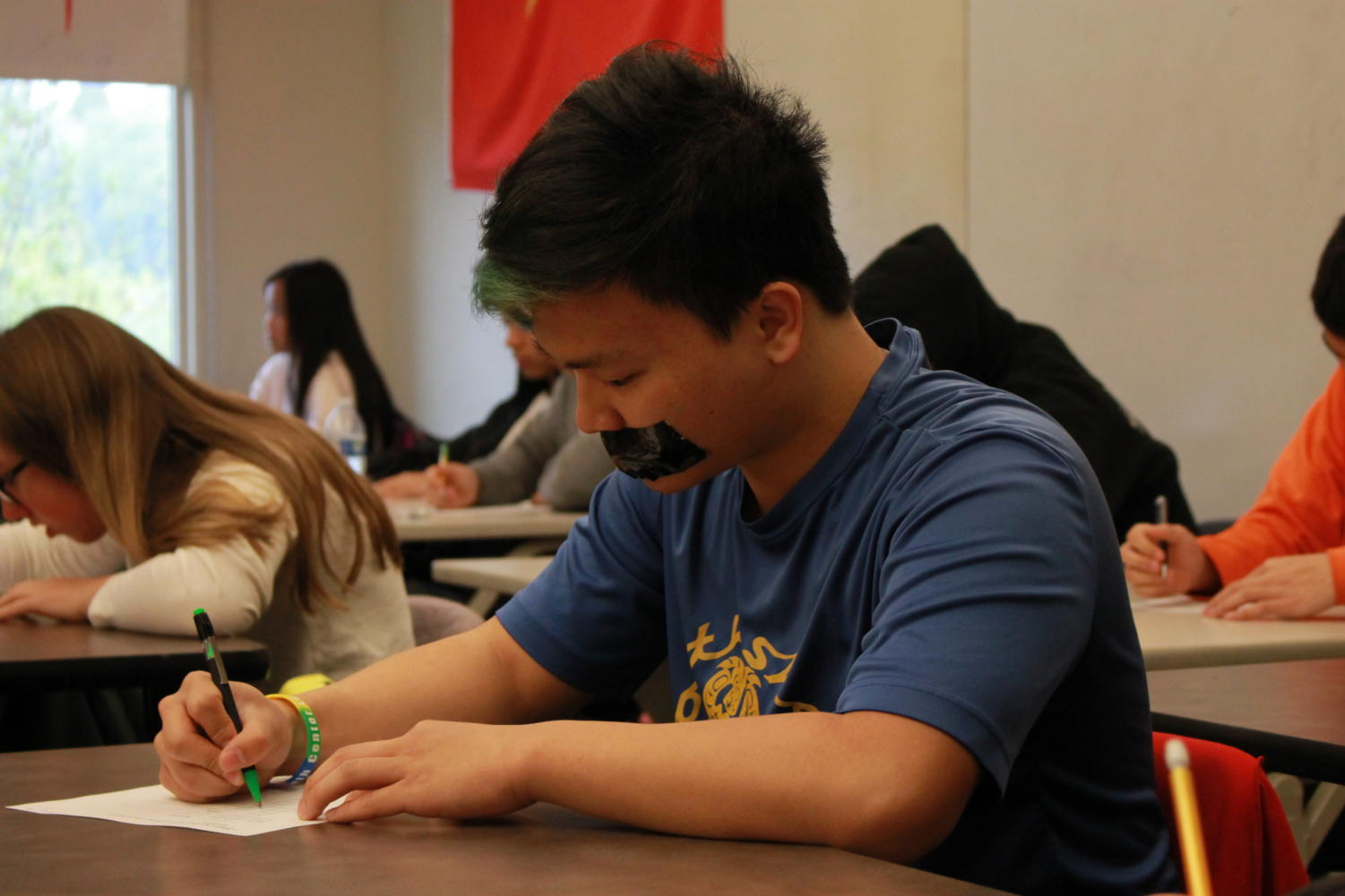 Junior Thang Dao starts to work on a Chinese test while participating in the Day of Silence.