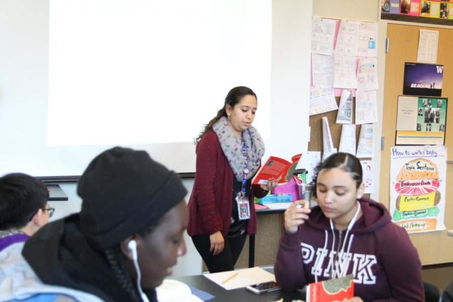 "Sophomore Humanities teacher Ana-Claudia Magaña reads ""Things Fall Apart"" to her students on Nov. 30. Magaña said recent shootings in places of worship have made it harder for her to feel safe when she attends church, but she tries not to focus on the negative."