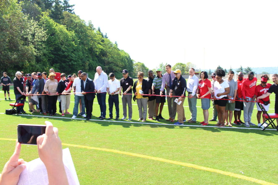 Cleveland coaches, staff members and government and school officials line up to cut the ribbon to declare the school's new playfield officially open at the field dedication on May 11.