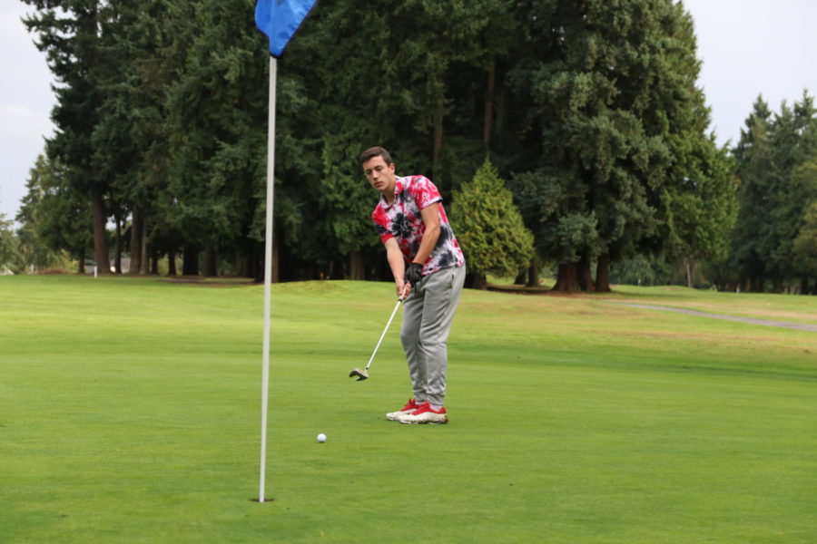 Senior Reed McFeely keeps his eyes on the ball as he watches his putt during a match against West Seattle at Jefferson Golf Course on Sept. 17.