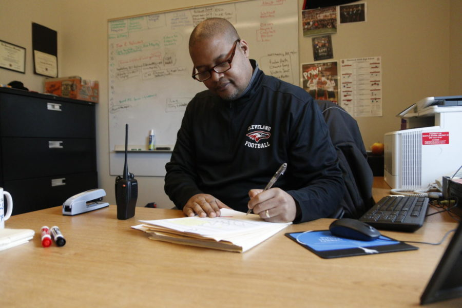 Principal George Breland signs off on some paperwork in his office on Nov. 7. Breland will undergo knee surgery, putting him on medical leave for about eight weeks.